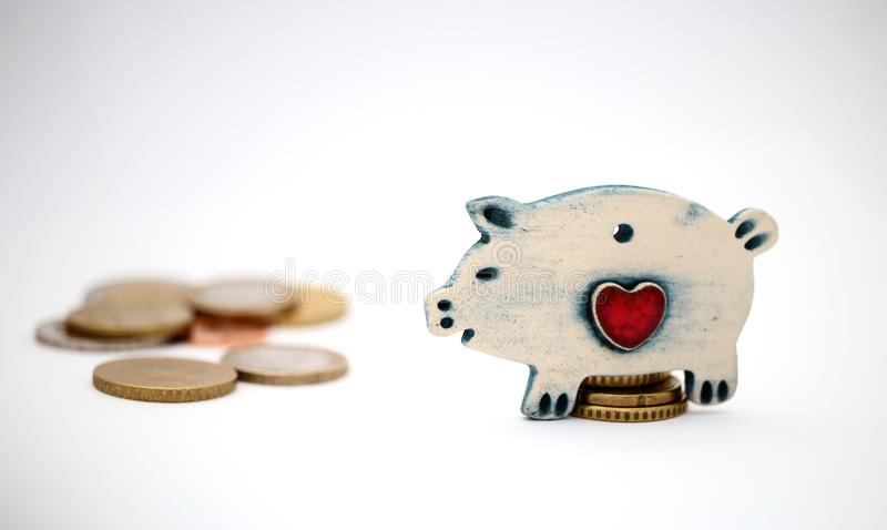 Ceramic piggy is sitting on savings. Next savings are in front of piggy. All isolated on white background.  stock photos