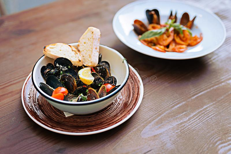 Luscious seafood dish lying in nice ceramic plate. Ceramic plate. Luscious yummy seafood dish with mussels and cherry tomatoes in creamy sauce lying in nice royalty free stock photo