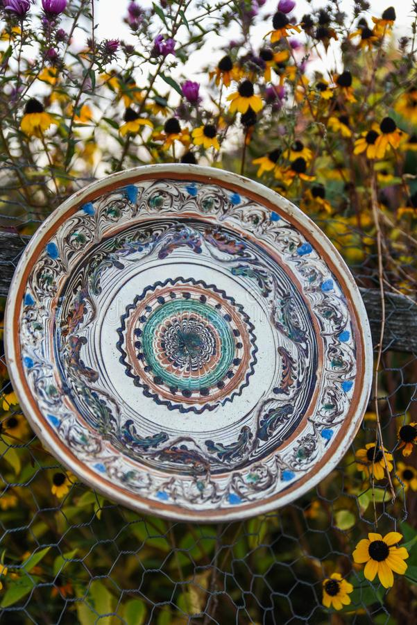 Ceramic plate and souvenir. Ceramic plates and souvenirs - Romanian pottery with flower background stock images