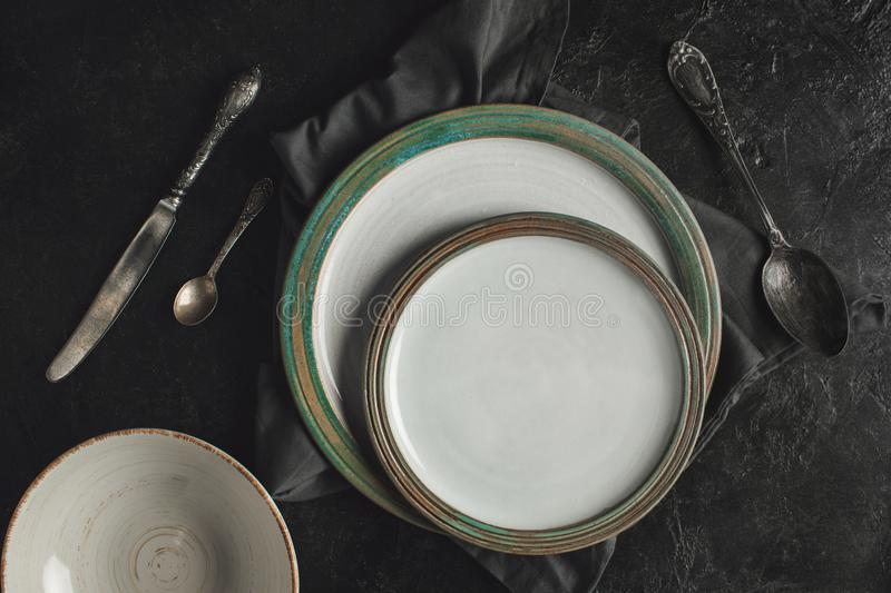 Ceramic plates and silverware. Top view of ceramic plates on linen and rustic silverware on black surface royalty free stock photography