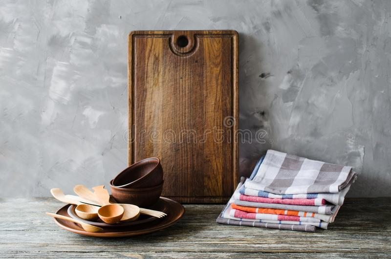 Ceramic plates, wooden or bamboo cutlery, vintage cutting board and towels in interior of kitchen stock photos