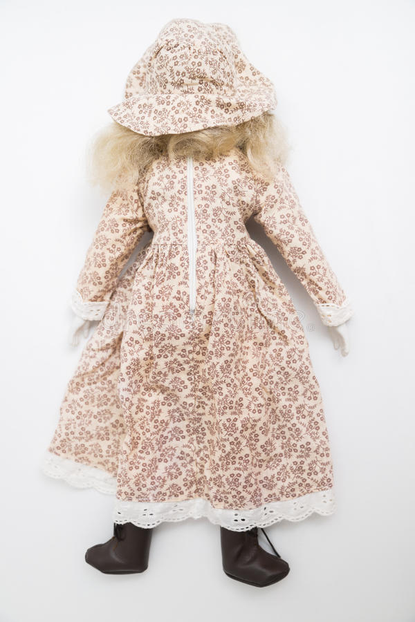 Ceramic porcelain handmade blond doll with textile hat and brown dress royalty free stock photos