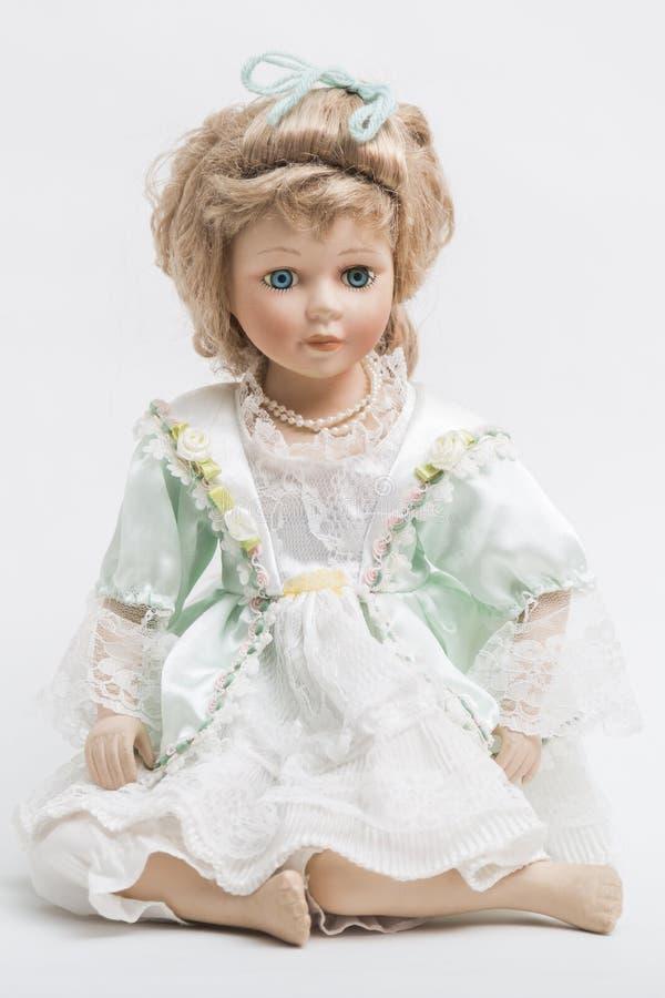 Ceramic porcelain handmade blond doll in white and green dress stock photo