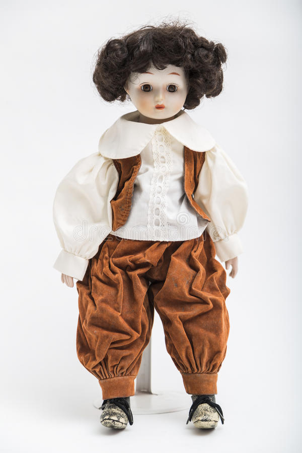 Ceramic porcelain handmade doll of a brunette boy in brown costume royalty free stock image