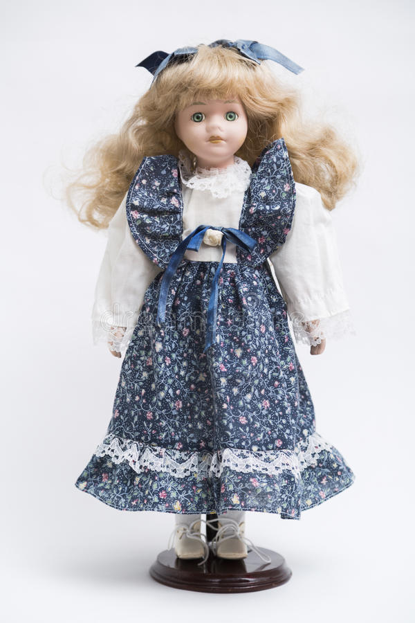 Ceramic porcelain handmade doll with long blond hair and blue dress stock images