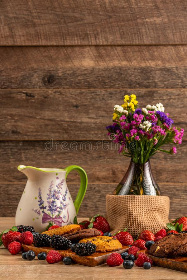 Ceramic pot, glass vase with flowers and cookies assorted with mix of wild berries royalty free stock photography
