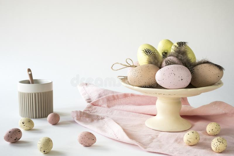 Ceramic stand with decorative Easter eggs on pink tablecloth, against white background. copy space stock photography