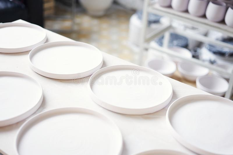 Ceramic studio, plane white clay plates ready to glaze and baking. stock photography