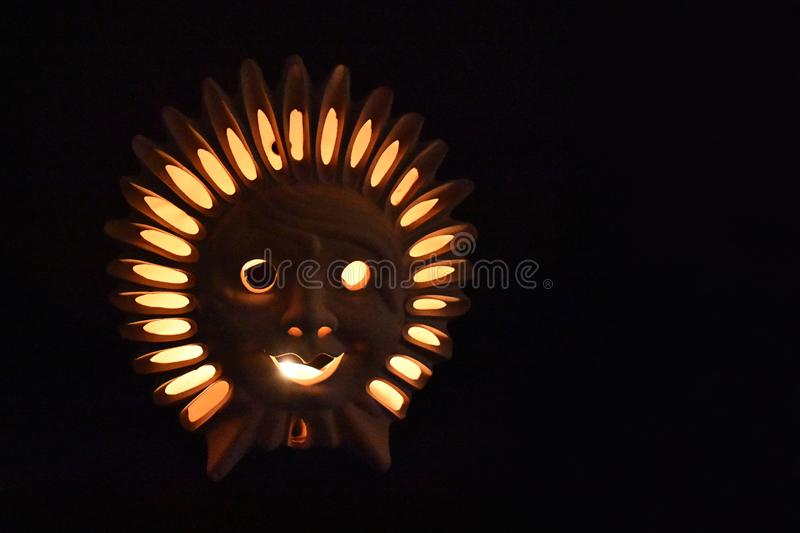 Ceramic Sun Face stock images. Glowing lamp on a dark background. Ceramic sun on a brown background. Ceramic Sun Lamp. Sun clay lamp stock photo