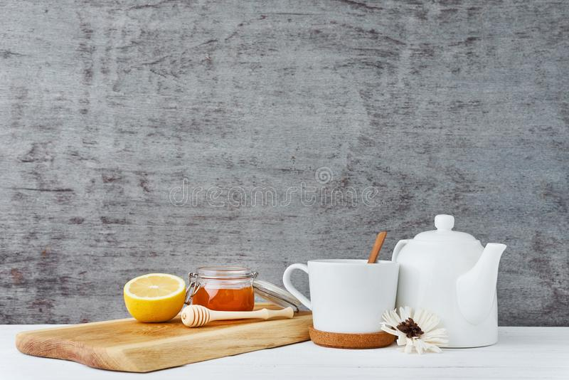 Ceramic teapot, white cup, honey in a glass jar and lemon on wooden background royalty free stock images