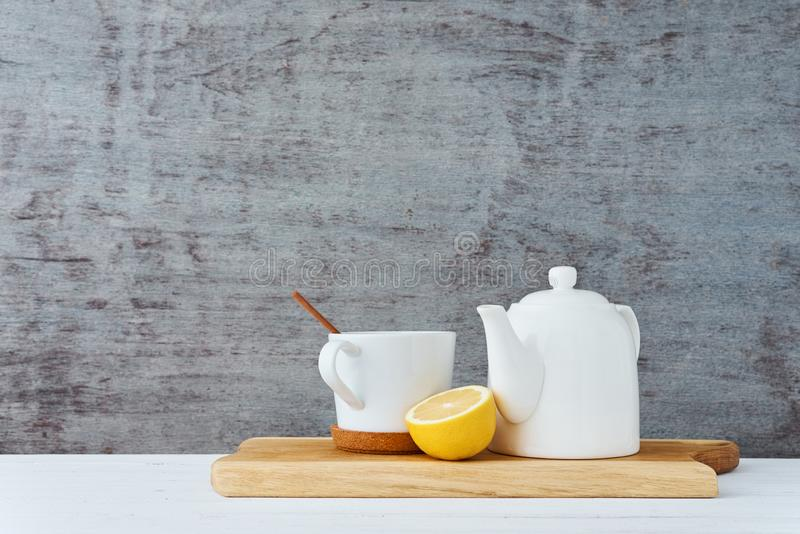 Ceramic teapot, white cup, honey in a glass jar and lemon on wooden background stock photos