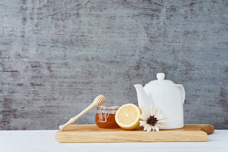 Ceramic teapot, white cup, honey in a glass jar and lemon on wooden background stock images