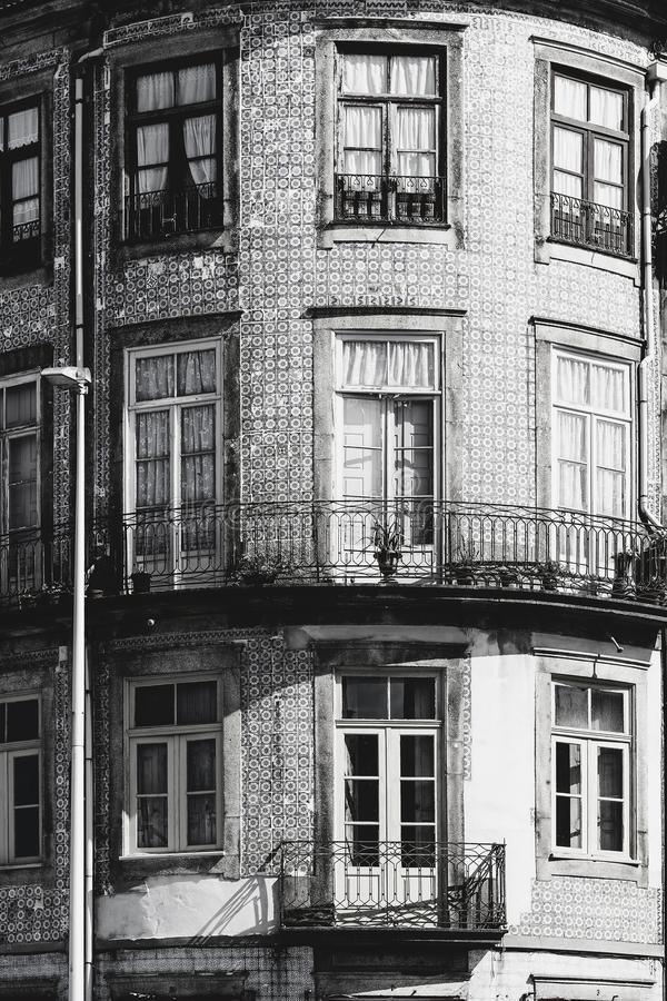 Ceramic tiles decorate a facade. Traditional Portuguese ceramic tiles of azulejo decorate a facade of the old house in the city of Porto. Black and white photo stock images