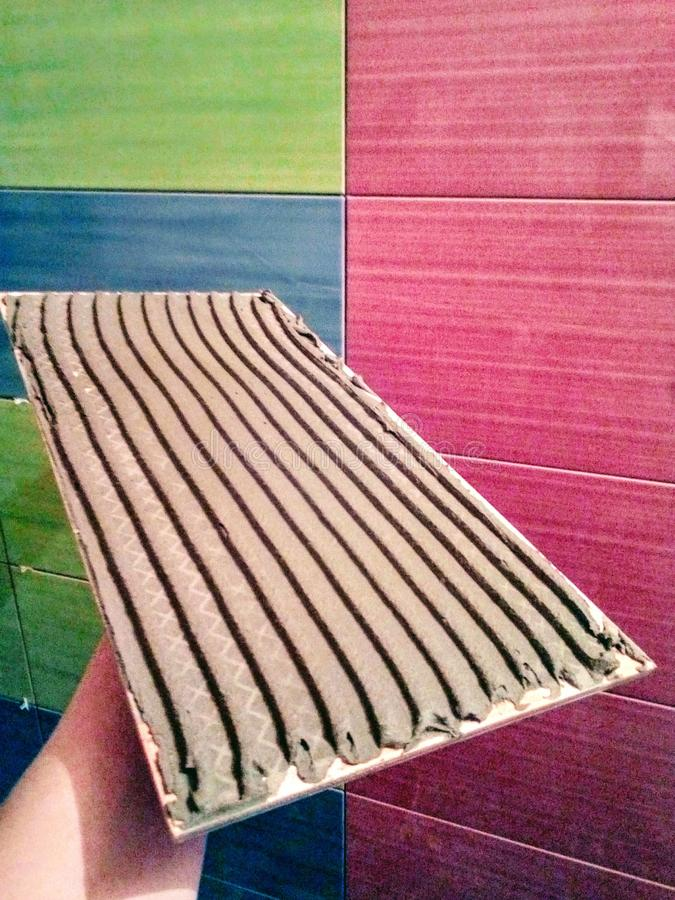 ceramic tiles finishing works repairs in the house work of the master mobile photo stock image