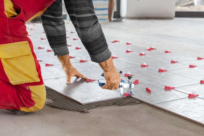 Ceramic Tiles. Tiler placing ceramic wall tile in position over adhesive with lash tile leveling system royalty free stock photo