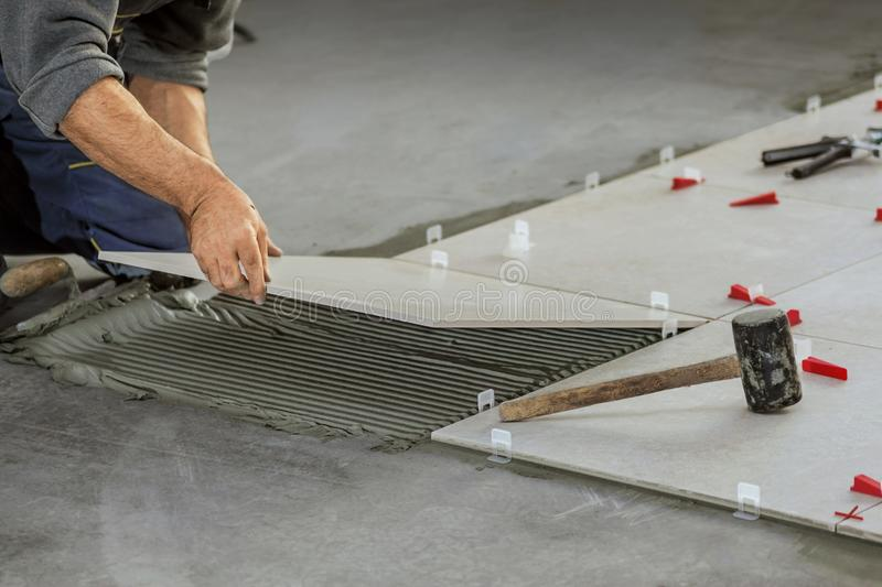 Ceramic Tiles. Tiler placing ceramic wall tile in position over. Adhesive with lash tile leveling system stock photos