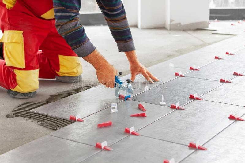 Ceramic Tiles. Tiler placing ceramic wall tile in position over adhesive with lash tile leveling system royalty free stock photos
