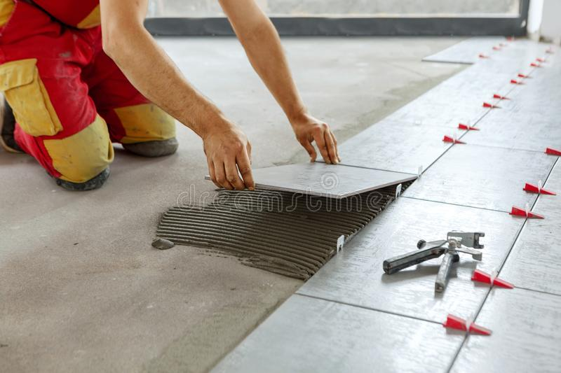 Ceramic Tiles. Tiler placing ceramic wall tile in position over adhesive with lash tile leveling system royalty free stock photography