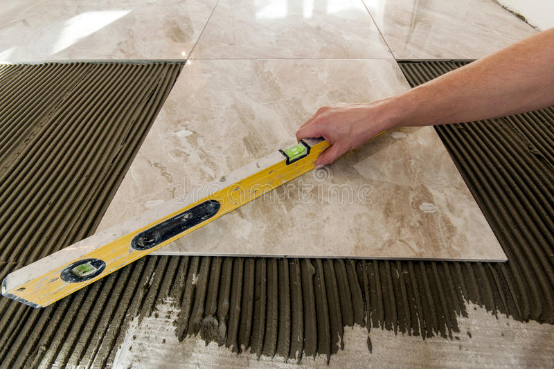 Ceramic tiles and tools for tiler. Floor tiles installation. Home improvement, renovation - ceramic tile floor. Adhesive, mortar, level stock photography
