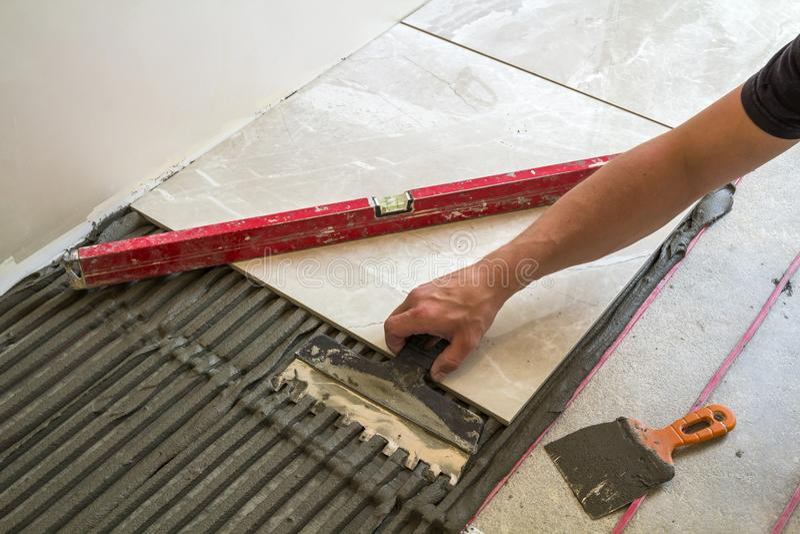 Ceramic tiles and tools for tiler. Worker hand installing floor tiles. Home improvement, renovation - ceramic tile floor adhesive, stock image