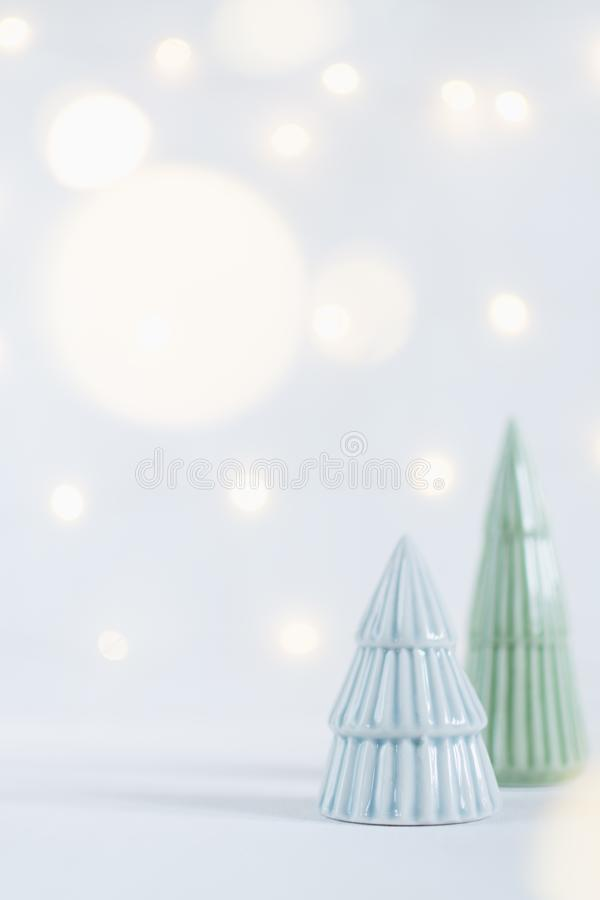 Ceramic toy christmas tree statuettes with garland bokeh on background. Shallow depth of field, vertical orientation royalty free stock photography