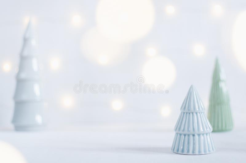 Ceramic toy christmas tree statuettes with garland bokeh on background. Shallow depth of field stock photography