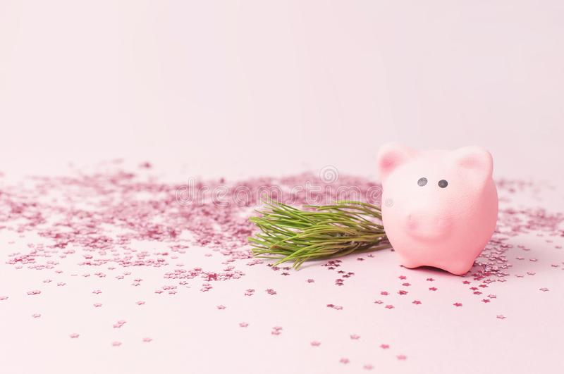 Ceramic toy pink pig symbol of the new year and holographic glitter confetti form of stars on pink background Flat Lay copy space royalty free stock image