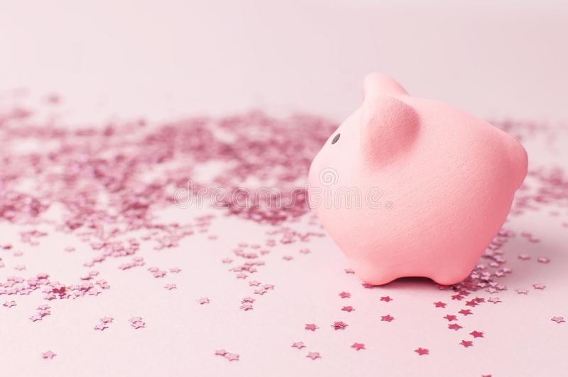 Ceramic toy pink pig symbol of the new year and holographic glitter confetti form of stars on pink background Flat Lay copy space. Decoration Festive decor stock photo