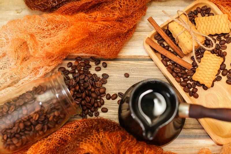 Ceramic turk, scarf, glass jar, cookies, cinnamon sticks and scattered coffee beans on vintage wooden table. Top view royalty free stock images