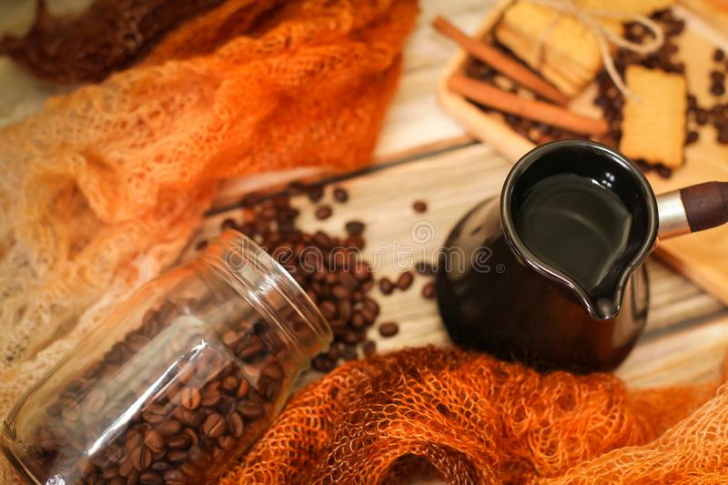 Ceramic turk, scarf, glass jar, cookies, cinnamon sticks and scattered coffee beans on vintage wooden table. Top view stock photos