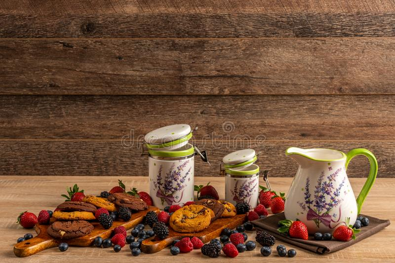 Ceramic vessels assorted with baked chocolate cookies and forest fruits on wooden background royalty free stock photo