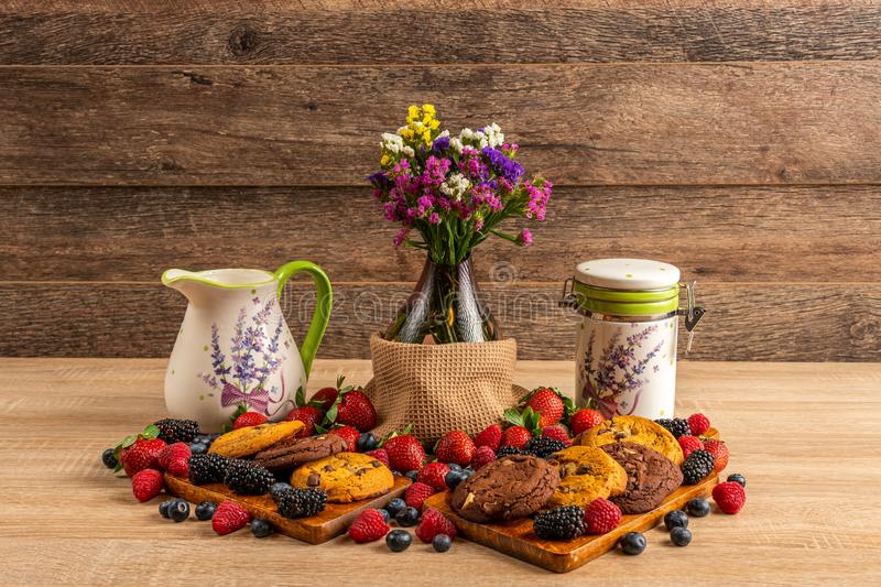 Ceramic vessels with assorted mix of forest fruits and flowers in vase royalty free stock images