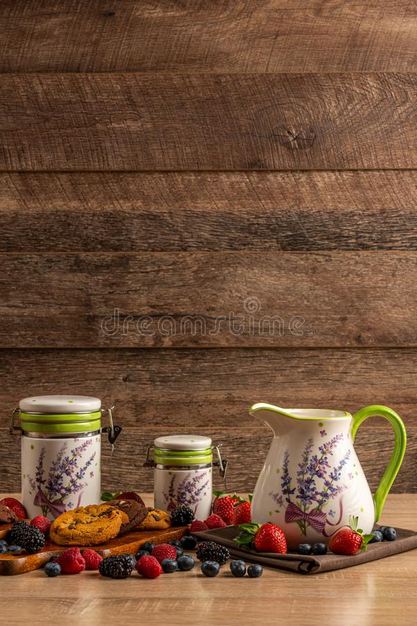 Ceramic vessels on wooden table assorted with cookies and forest fruits with copy space above stock images