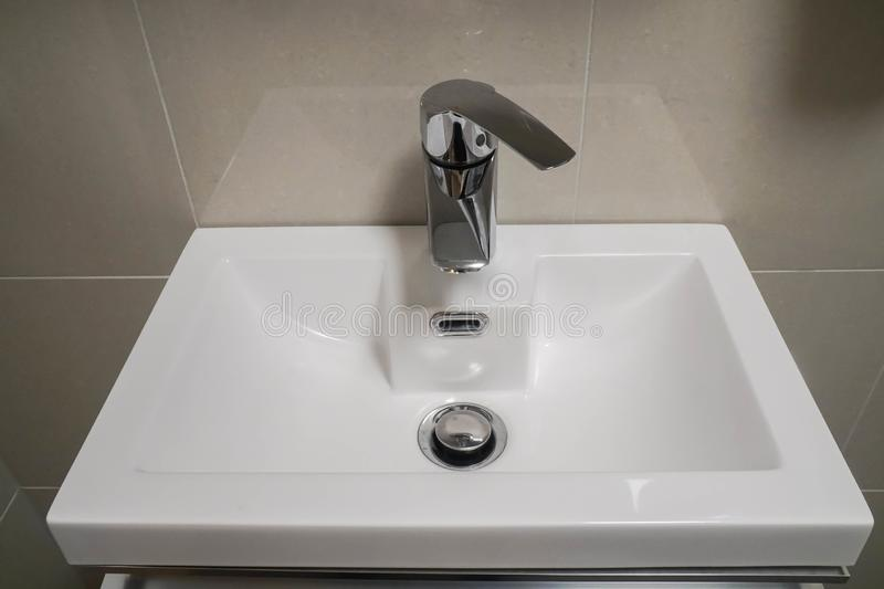 Ceramic washbasin with hot and cold faucet in luxury hotel bathroom stock photography