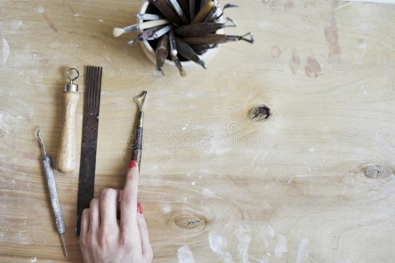 Ceramic working process, tools for hand-crafted work in woman hand. View from above, wooden table. stock photos
