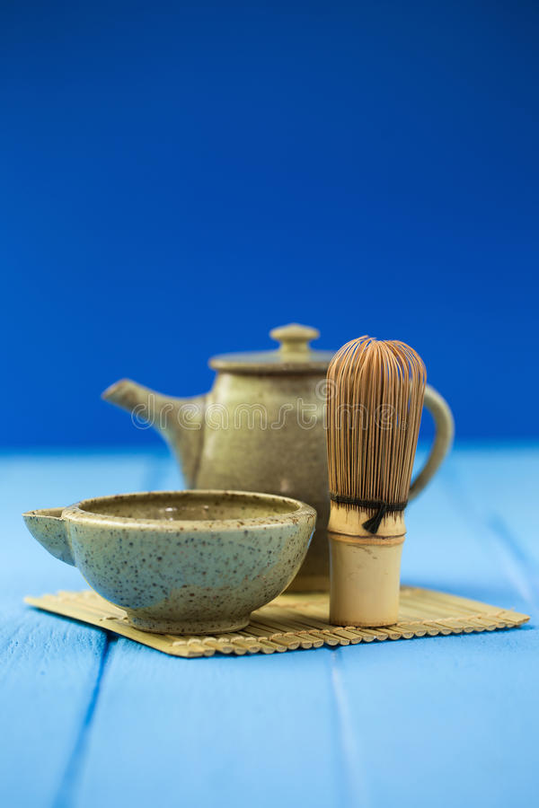 Ceramics bowl and chasen - special bamboo matcha tea whisk, lying on blue wooden background. royalty free stock images