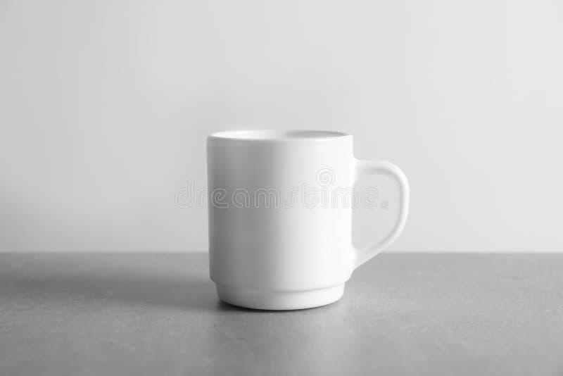 Ceramiczna filiżanka na stole przeciw białemu tłu zdjęcie stock