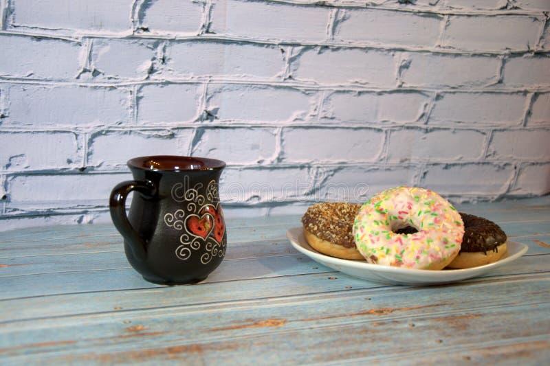Ceramiczna fili?anka z herbat? i bia?ym porcelana talerzem z donuts w lodowaceniu Zako?czenie fotografia royalty free