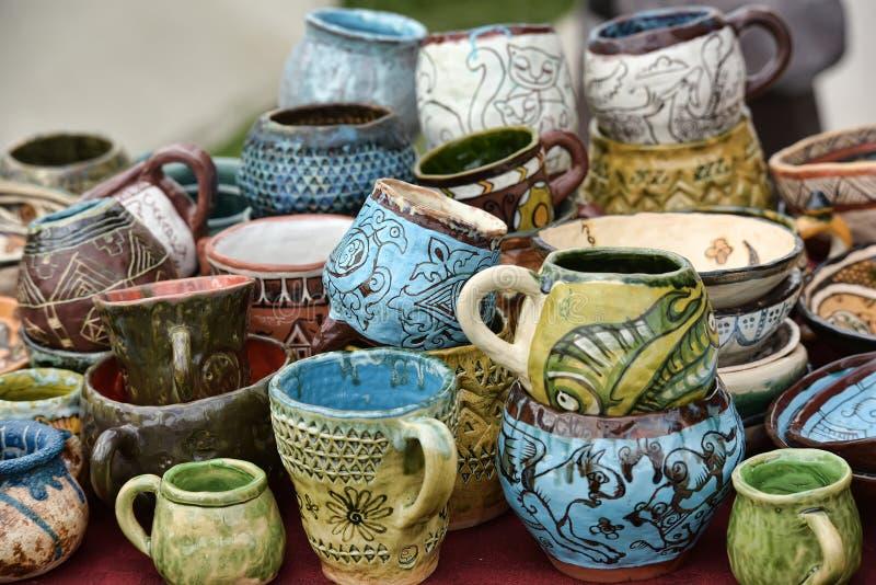 Ceramiczne filiżanki i puchary z śmiesznymi rysunkami fotografia stock