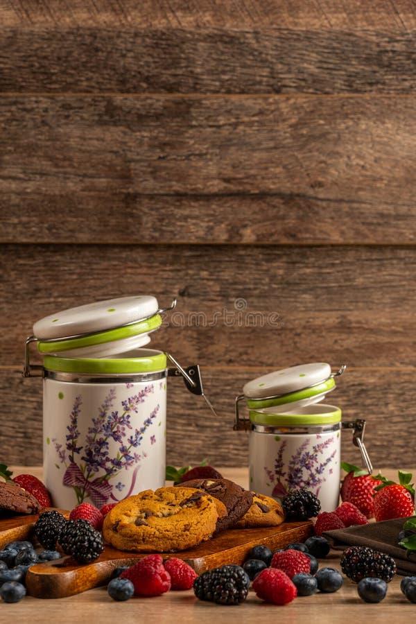 Ceramiczni słoje z ciastkami i las owoc na drewnianym stole z kopii przestrzenią obrazy stock