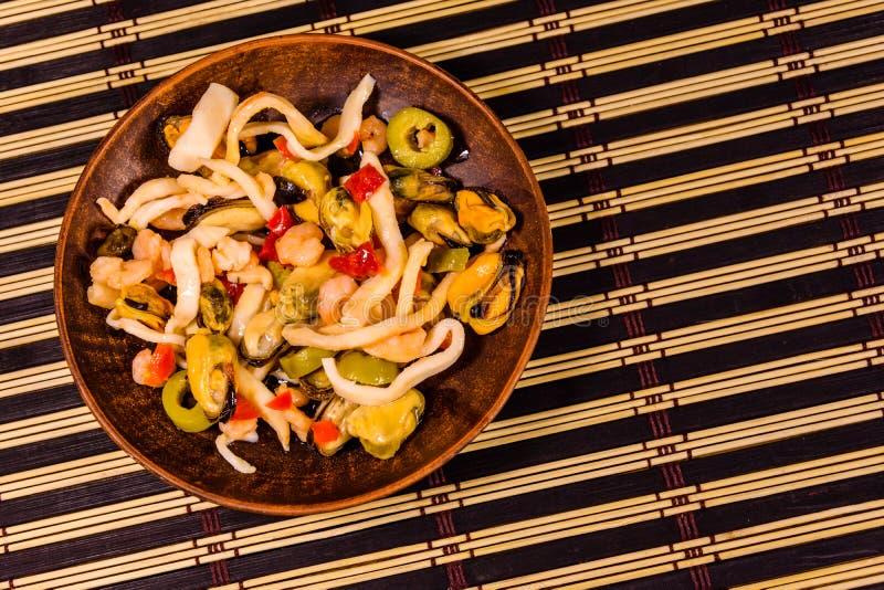 Ceramiczny talerz z różnym dennym jedzeniem i oliwki na bambusie matujemy obrazy royalty free