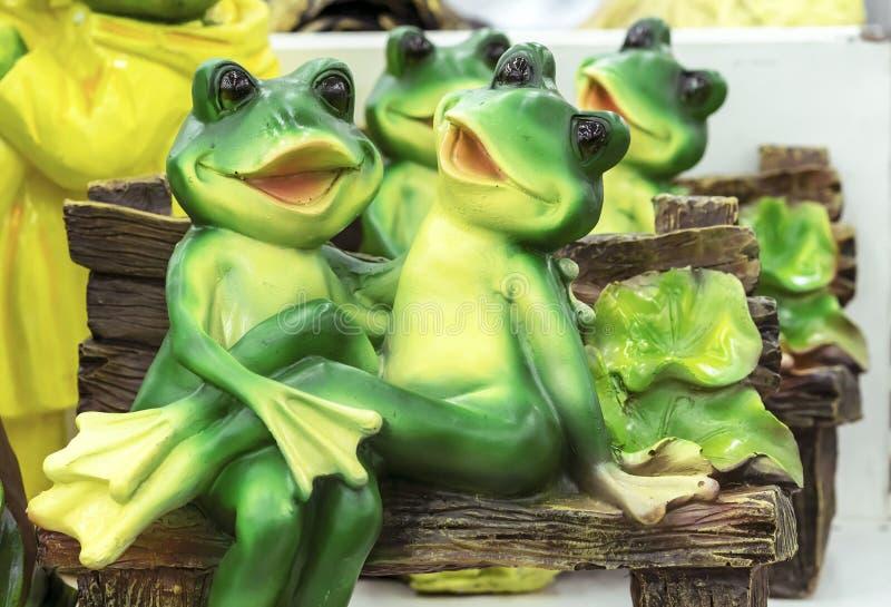 Ceramisch beeldje van kikkers gezet in een greep op een bank stock afbeeldingen