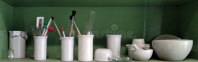 Ceramisch chemisch glaswerk voor experimenten op de plank stock foto