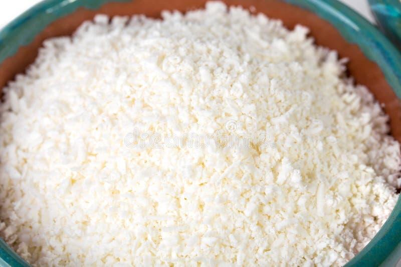 Ceramisch komhoogtepunt van verse geraspte kaas stock foto