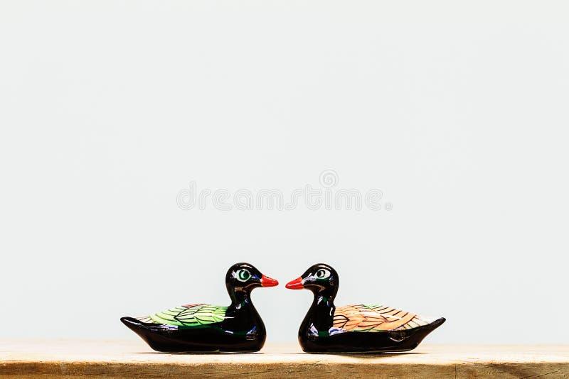 Ceramisch zwart eendbeeldje op houten lijst aangaande witte achtergrond royalty-vrije stock afbeelding