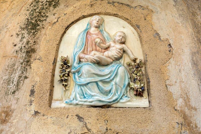 Ceramische bas-hulp van Maagdelijke Mary met Jesus op de muur van het huis in Ravello Amalfi Kust stock afbeelding