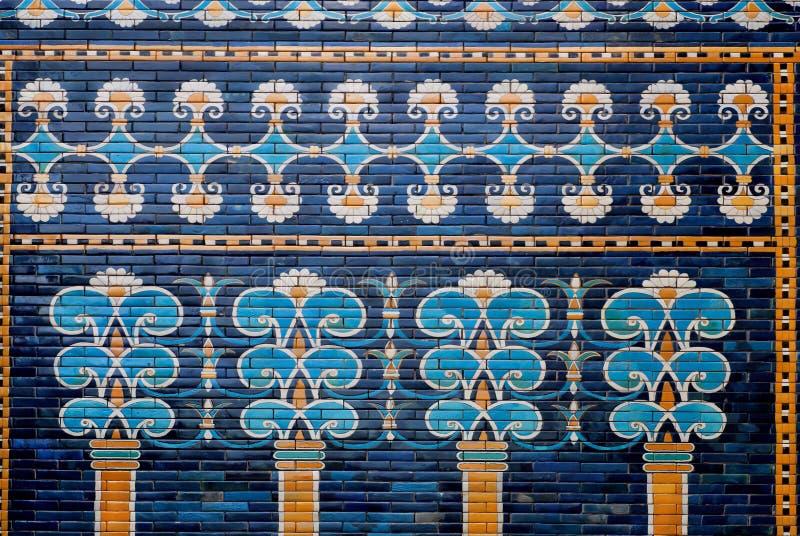 Ceramische deklaag met beelden van bomen en patronen op de historische muur van Babylon stock afbeelding