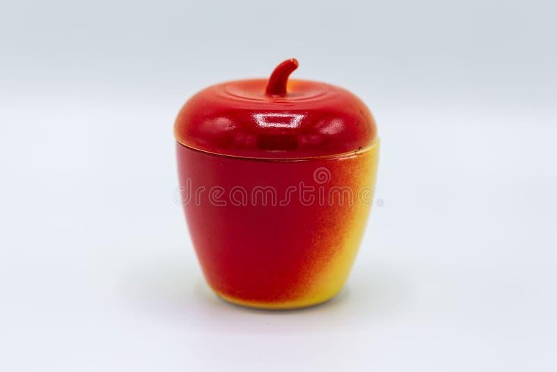 Ceramische die kruik met deksel wordt gevormd om als een rode appel te kijken stock fotografie