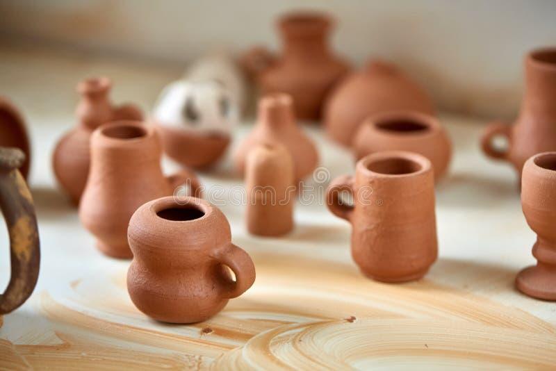 Ceramische dishware op worktop en planken in aardewerkworkshop, selectieve nadruk, close-up stock foto
