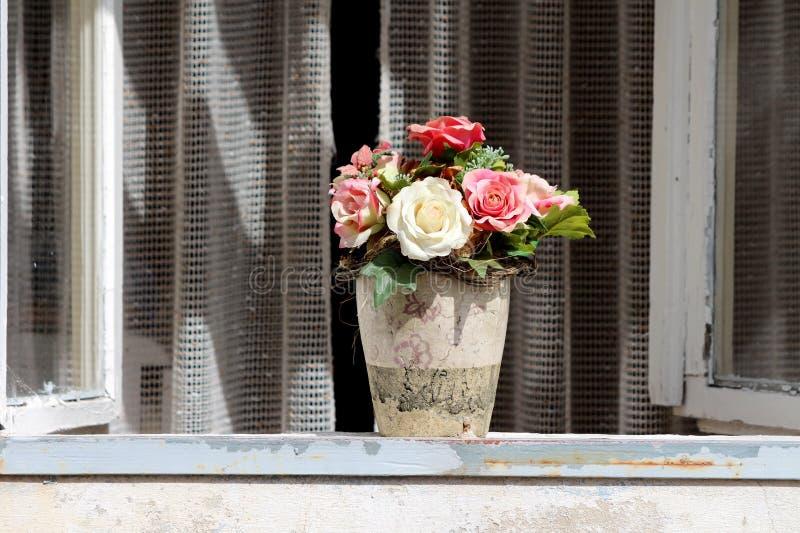 Ceramische gedeeltelijk gebroken bloemvaas met plastic rozen in diverse kleuren bovenop vensterverbinding met open binnen venster stock afbeelding